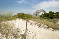 Casa pequena da casa de campo da cabine no litoral do oceano na grama e na areia em um dia ensolarado da reentrância Foto de Stock