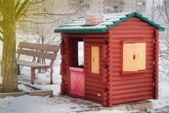 A casa pequena do ` s das crianças está na rua coberta com a neve, winte Fotos de Stock Royalty Free