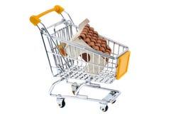 Casa pequena em um carro do supermercado em um fundo branco fotos de stock
