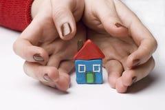 Casa pequena entre as mãos fotografia de stock royalty free