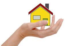 Casa pequena na mão humana, isolada no fundo branco Imagens de Stock Royalty Free