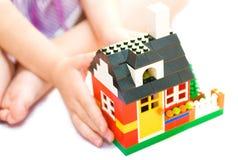 A casa pequena nas mãos da criança Imagem de Stock