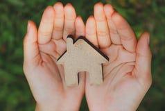 Casa pequena nas mãos das mulheres no fundo natural imagens de stock royalty free