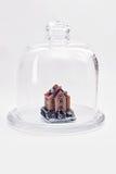 Casa pequena sob a proteção de uma tampa de vidro Foto de Stock Royalty Free