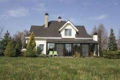 Casa privata con un giardino in una zona rurale sotto il bello cielo Fotografia Stock Libera da Diritti