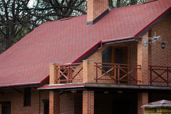 Casa privata moderna del mattone con il tetto rosso in primavera Immagini Stock Libere da Diritti