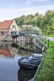 Casa, puente y balandro reflejando en canal fotografía de archivo