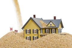 Casa que afunda-se na areia rápida com para o sinal do aluguel e a ajuda da palavra escritos na areia Imagem de Stock