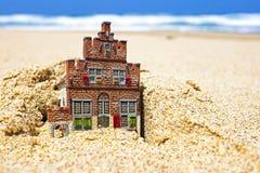 Casa que desaparece en la arena. Imagen de archivo libre de regalías