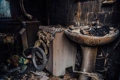 Casa queimada interior Banheiro queimado queimado, sobras fundidas da mob?lia e m?quina de lavar fotografia de stock royalty free