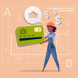 Casa Real Estate de la venta de Hold Credit Card del constructor de la mujer de la historieta sobre hembra afroamericana del fond Fotos de archivo libres de regalías
