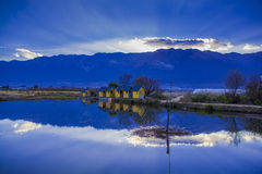 Casa reflejada en el lago cerca de la montaña Foto de archivo
