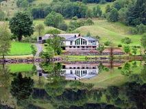 Casa refletida no lago Riskedalsvatnet Fotos de Stock Royalty Free