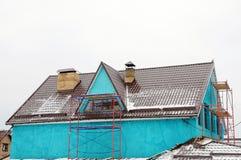 A casa repara fora Calha na parte superior do telhado da casa Telhado do metal Protetores da neve do telhado Tubulação da chaminé Imagens de Stock Royalty Free