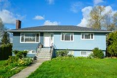 Casa residencial com jardim da frente ajardinado no fundo do céu azul Imagens de Stock Royalty Free