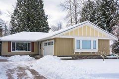 Casa residencial con el jardín en nieve el día de invierno fotos de archivo