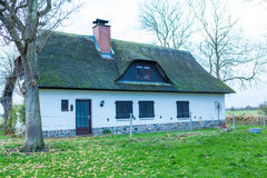 Casa residencial con un tejado cubierto de musgo verde de la paja Fotos de archivo libres de regalías