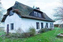 Casa residencial con un tejado cubierto de musgo verde de la paja Fotografía de archivo libre de regalías