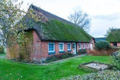 Casa residencial con un tejado cubierto de musgo verde de la paja Imagenes de archivo
