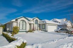 Casa residencial en nieve en día de invierno soleado Imagenes de archivo