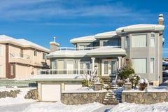 Casa residencial luxuosa com a garagem dobro no dia ensolarado do inverno imagem de stock