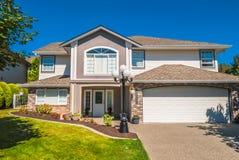 Casa residencial luxuosa com gramado da grama na parte dianteira Fotografia de Stock Royalty Free