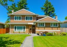Casa residencial média na vizinhança perfeita Casa da família fotografia de stock royalty free