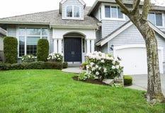 Casa residencial na estação de mola meados de com flores de florescência e Fotos de Stock Royalty Free