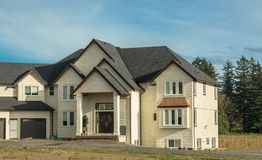 Casa residencial nova gigante com a entrada de automóveis unpaved na parte dianteira Fotos de Stock