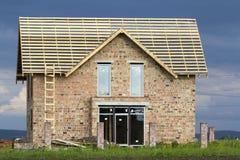 Casa residenziale a due piani con le finestre di plastica, l'ampia porta e la struttura di legno per il tetto in costruzione Alta Fotografia Stock Libera da Diritti