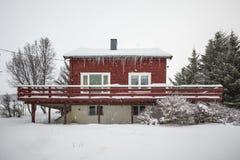 Casa roja ártica tradicional típica con nieve y el carámbano Imagen de archivo libre de regalías