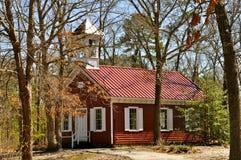 Casa roja de la escuela en las maderas Imagen de archivo libre de regalías