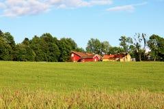 Casa roja en el prado verde Fotos de archivo libres de regalías
