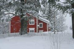 Casa roja en nieve Imagen de archivo libre de regalías