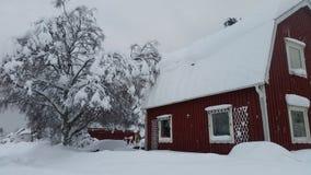 Casa roja en nieve Fotos de archivo libres de regalías