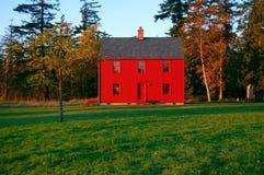 Casa roja en un campo verde Fotos de archivo