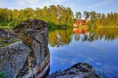 Casa roja y la roca del lago Imagen de archivo libre de regalías