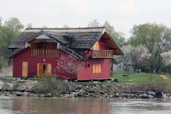 Casa rossa da un lato del fiume Fotografia Stock