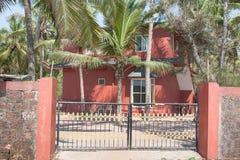 Casa rossa dietro una rete fissa Fotografia Stock Libera da Diritti