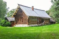 Casa rural com gramado verde no jardim da frente na floresta entre árvores imagem de stock