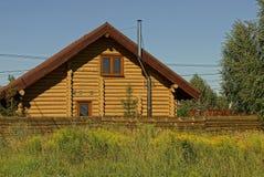 Casa rural com uma janela dos logs atrás de uma cerca na grama Foto de Stock