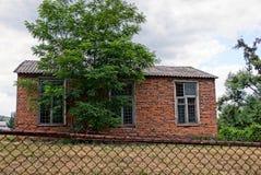 Casa rural del ladrillo detrás de un árbol verde en la yarda Fotografía de archivo libre de regalías