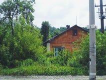 casa rurale sui precedenti degli alberi e dei cespugli verdi Immagini Stock