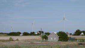 Casa rurale sui precedenti dei generatori eolici enormi stock footage