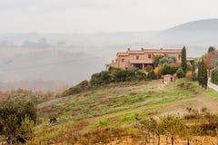 Casa rurale toscana su una collina in un giorno nebbioso, Toscana, Italia Fotografie Stock Libere da Diritti