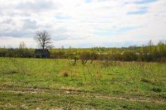 Casa rusa por la hierba verde, gris azul, cielo nublado de Orthern Fotografía de archivo