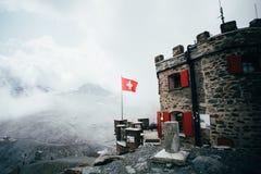 Casa scenica del rifugio con la bandiera dello svizzero Fotografia Stock Libera da Diritti