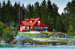 Casa septentrional roja en bosque Imagen de archivo libre de regalías