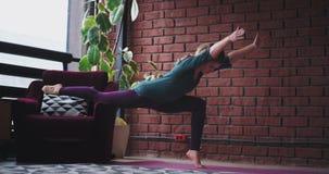 A casa signora nell'yoga di pratica del salone per la meditazione lei che per mezzo di un sofà per sostenere le gambe in questo e stock footage