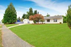 Casa simples exterior na cor branca com jardim da frente verde Imagem de Stock